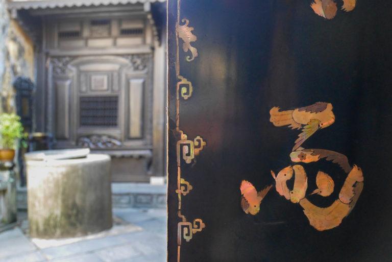 Litery w kształcie ptaków i dziedziniec ze studnią