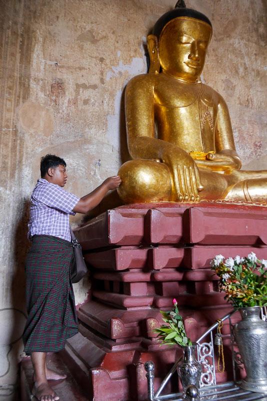 Mężczyzna przykleja złoty listek na pomnik Buddy