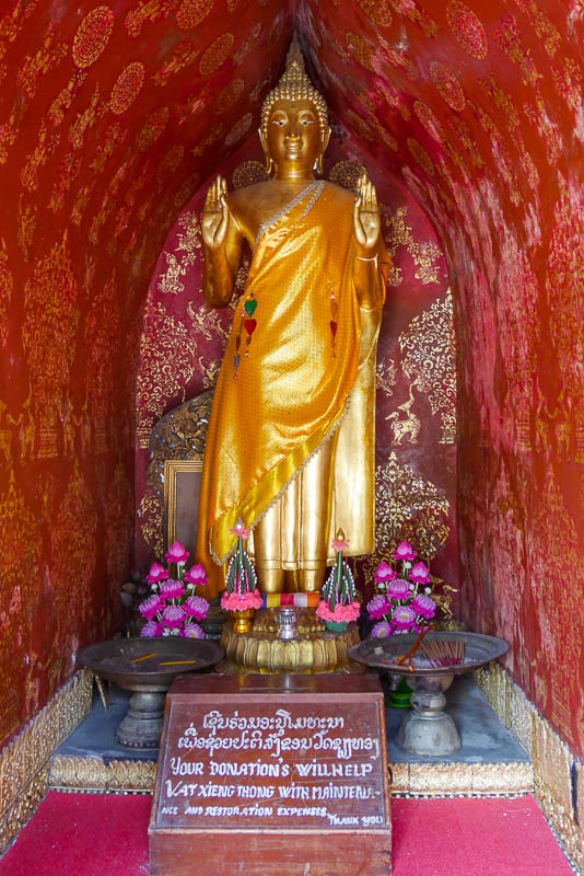 Stojący Budda, który nad głową ma namalowane koła Dharmy