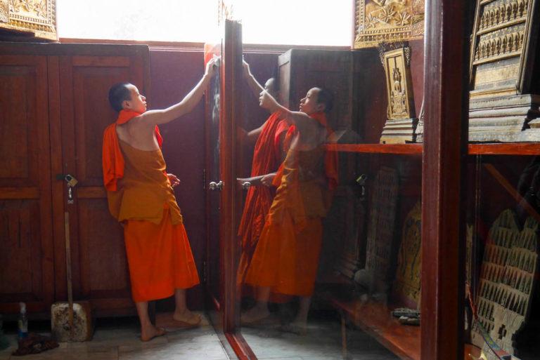 Mnisi sprzątają pomieszczenia Wat Xieng Thong