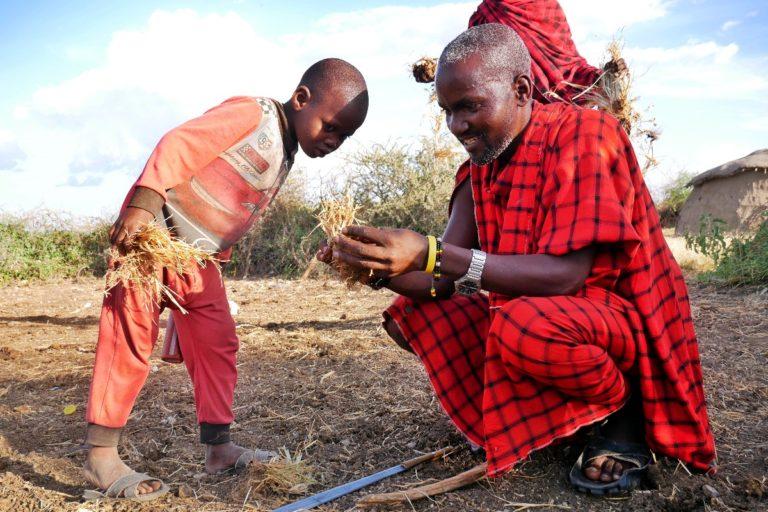 Szef masajskiej wioski pokazuje jak rozpalić ogień z użyciem dwóch kawałków drewna
