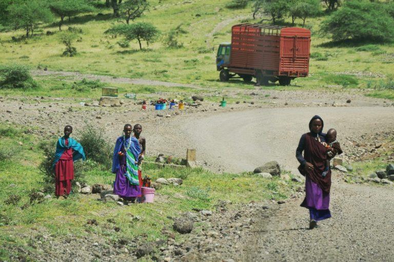 Masajski kobiety sprzedają miód na drodze