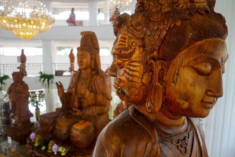 Rzeźby wykonane z drzewa sandałowego stoją wewnątrz kolorowej pagody