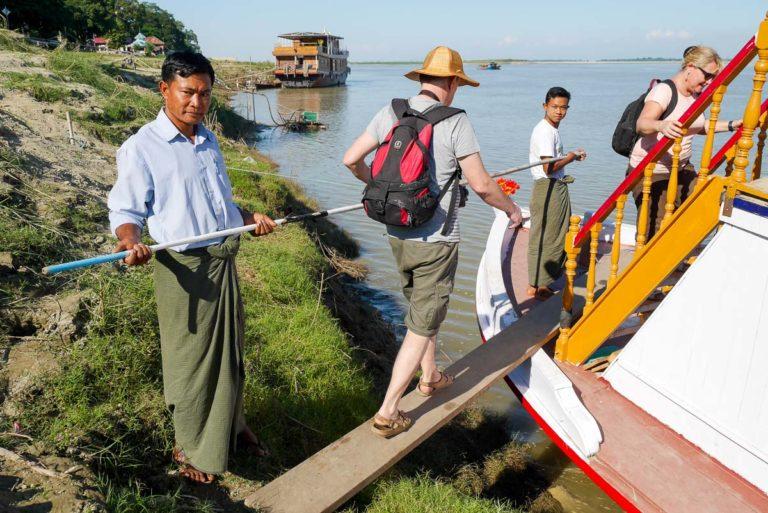 Mężczyźni obsługujący turystów na statku w Mandalay ubrani są w longyi